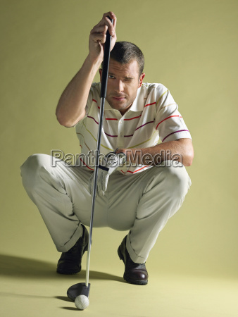 golfer squatting with club and ball