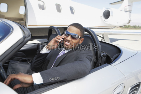 businessman using cell phone in convertible