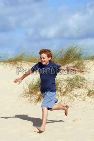 boy running on sand at beach