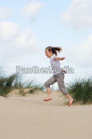 girl running on sand at beach