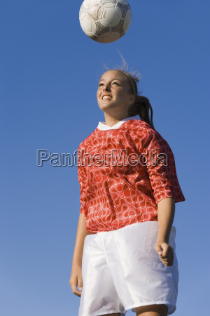 woman heading the soccer ball