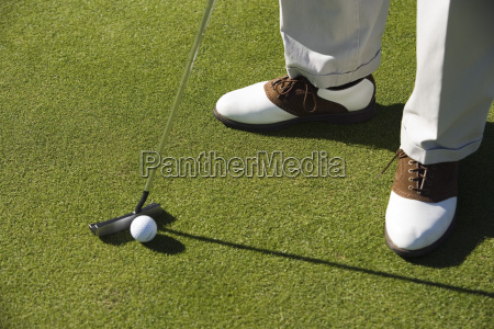 legs with golf club and ball