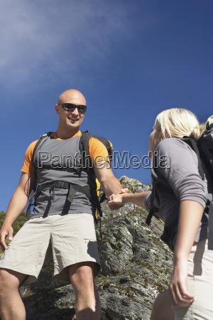 man helping woman climb onto a