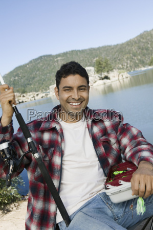 man sitting with fishing rod and