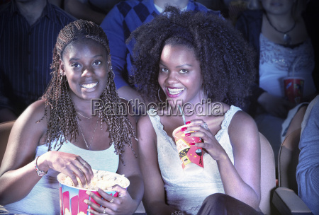 female friends with drink and popcorn
