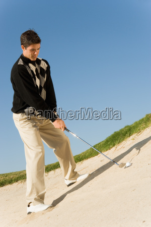 male golfer about to hit ball