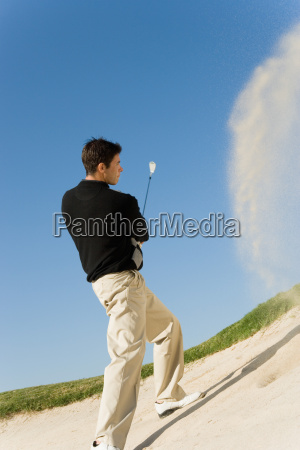 man chipping golf ball out of