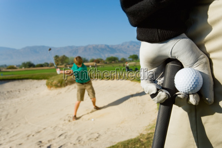 golfer holding ball with man playing