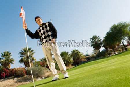 male golfer holding flag and golf