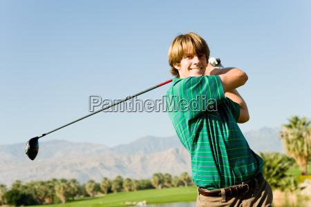 happy male golfer swinging golf club