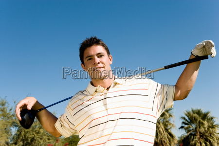confident young man with golf club