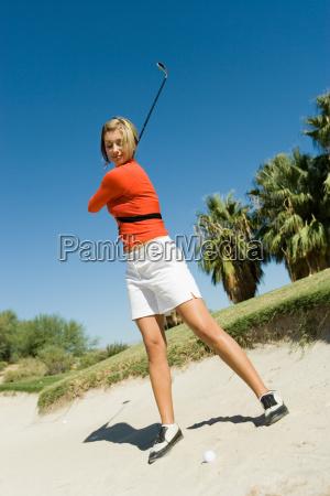 female golfer hitting ball from sand