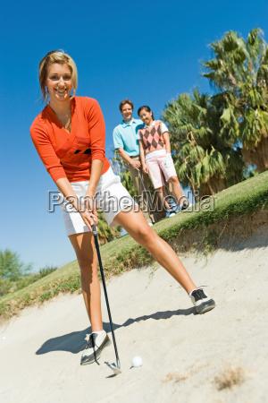 weiblicher golfer trifft ball aus sandfalle