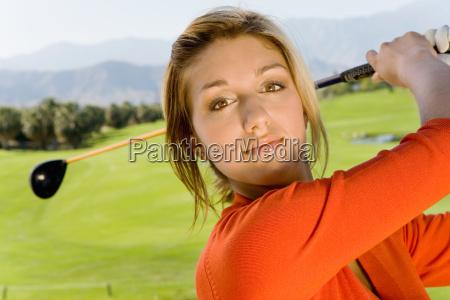 young woman swinging golf club