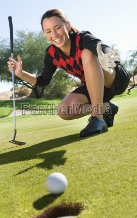 golfer with ball rolling towards cup