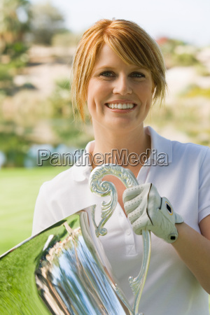 happy female golfer holding trophy