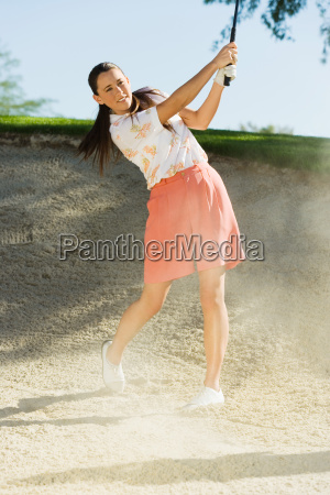 woman hitting golf ball out of
