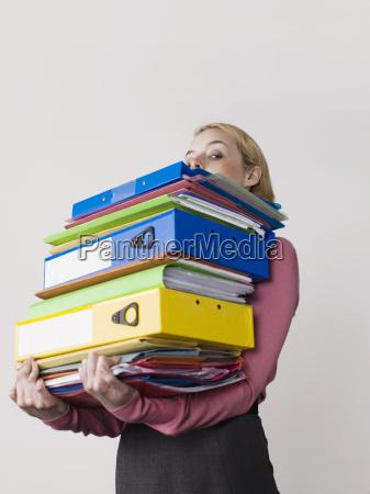 junger, weiblicher, büroangestellter, der, schwere, mappen, trägt - 21391885