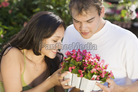 couple holding potted plants