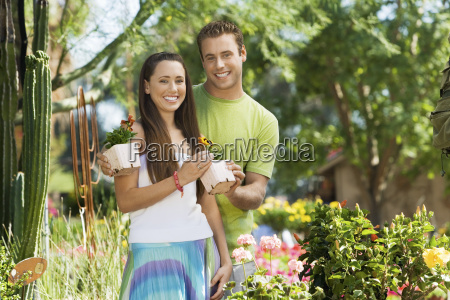 young couple holding potted plants