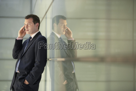businessman using mobile phone while leaning