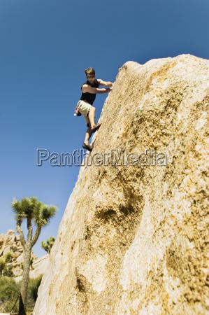 man free climbing on cliff