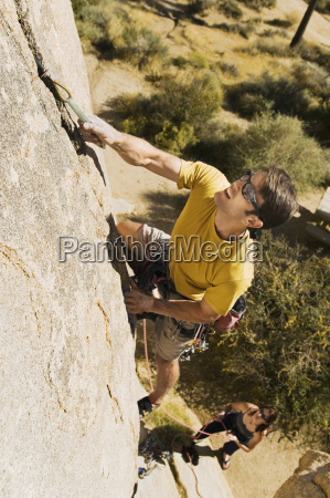 determined man climbing rock