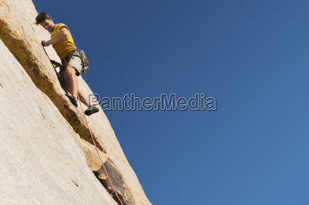 man climbing on cliff