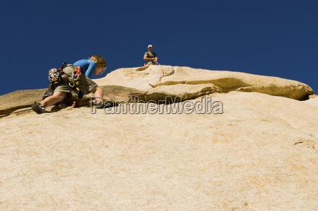 man assisting friend climbing rock against