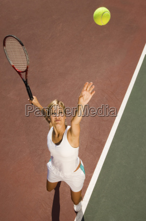 female tennis player serving ball on