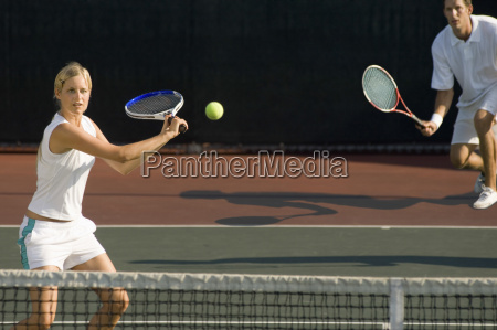 tennis player hitting ball with partner