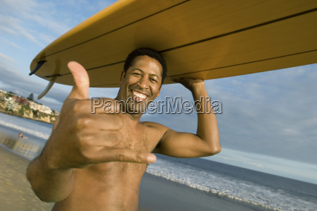 man gesturing while carrying surfboard on