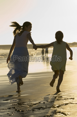 mother and daughter running on beach