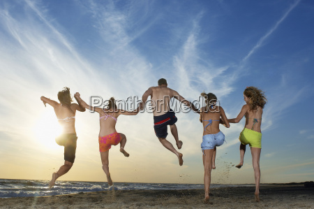 friends jumping on sand while holding
