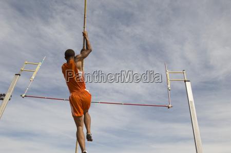 maennlicher athletder einen stabhochsprung durchfuehrt