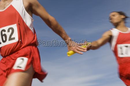 athleten die taktstock im staffellauf fuehren