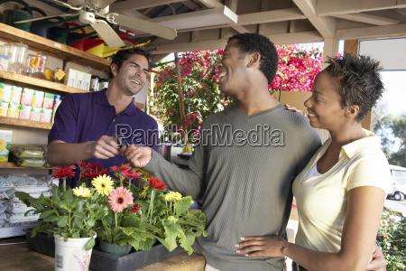 couple paying for plants in nursery