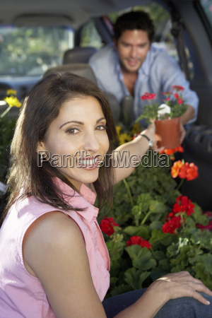 couple keeping flower plant in cars