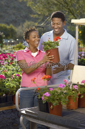 couple loading potted plants on golfcart