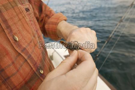 man putting bait on fishing hook