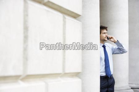 businessman using mobile phone by pillar