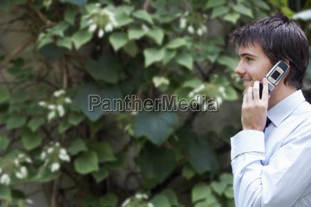 businessman using mobile phone in garden