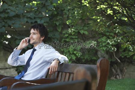businessman using mobile phone on park