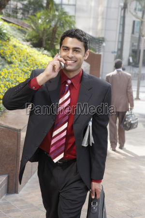 businessman using mobile phone on city