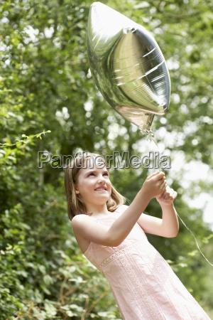 kleines maedchen mit ballon im park