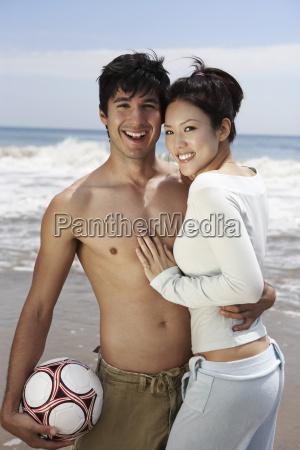 happy couple holding football on beach