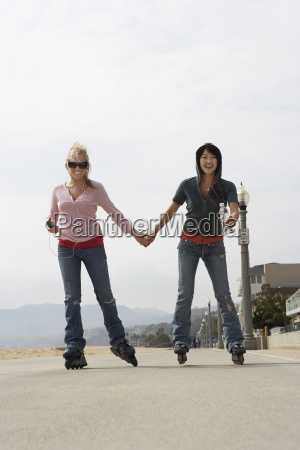 young women rollerblading on street
