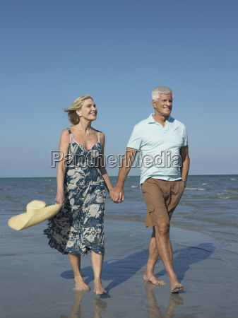 romantic senior couple walking on beach