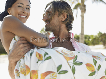 happy man carrying woman on beach