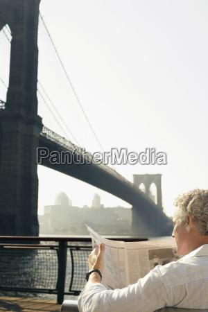 man reading newspaper by brooklyn bridge